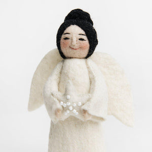 A Craftspring handmade felt angel ornament with black hair up in a bun wearing white robes and holding a beaded white star