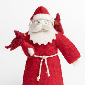 A Craftspring handmade felt father Christmas ornament wearing a red robe and santa hat with two cardinals roosting on him