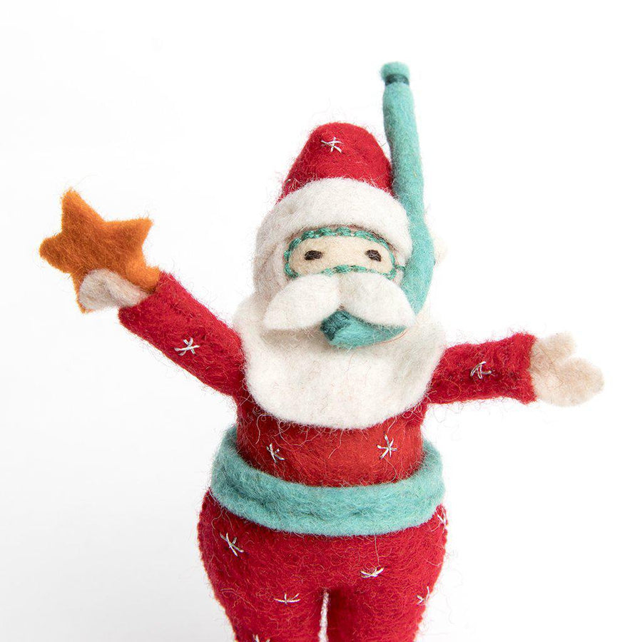A Craftspring handmade tropical snorkel scuba santa ornament wearing a red scuba suit and holding a little orange starfish