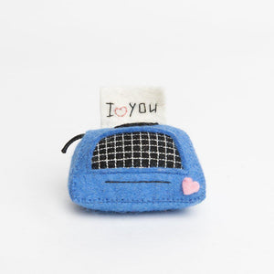 A Craftspring handmade blue felt typewriter ornament with a note embroidered with I Heart You