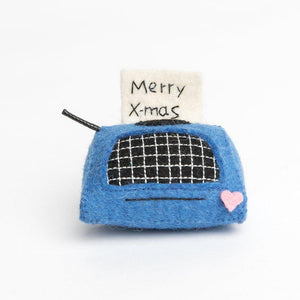A Craftspring handmade blue felt typewriter ornament with an embroidered note merry x-mas