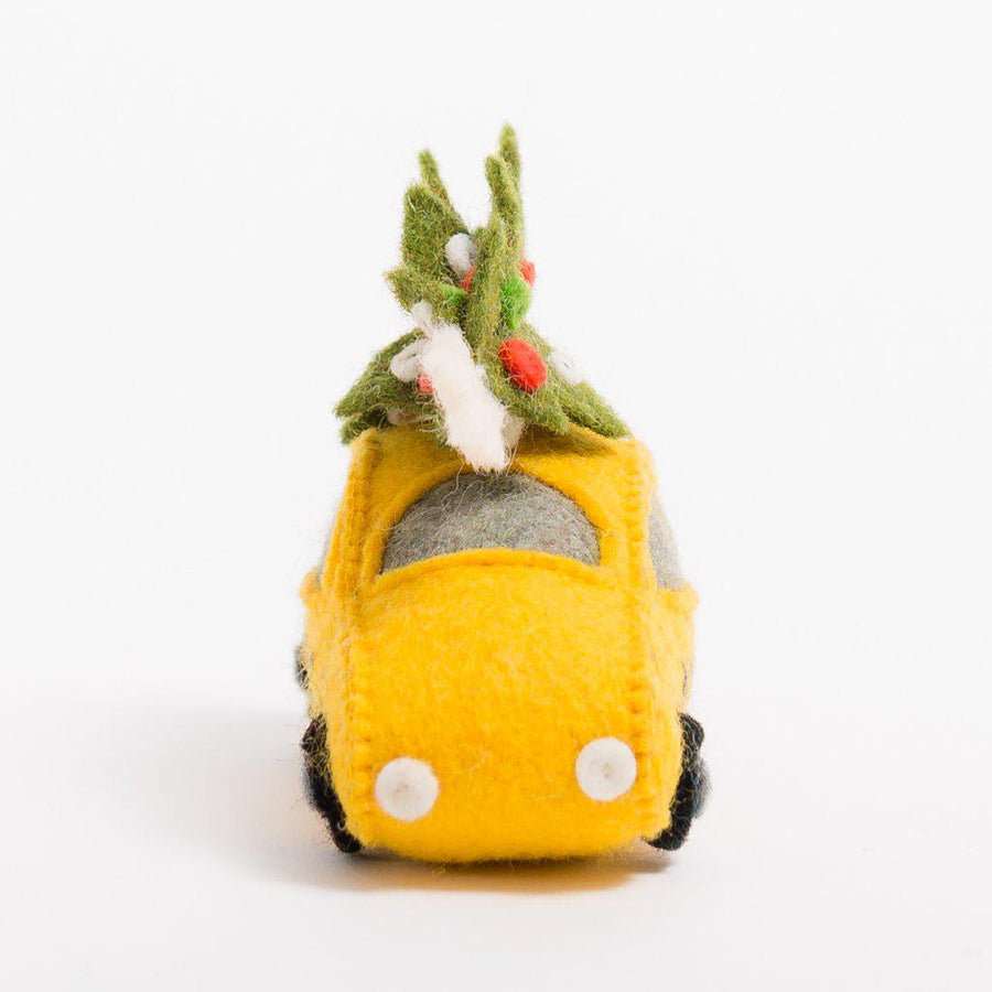 A Craftspring handmade felt taxi ornament with a decorated christmas tree on top