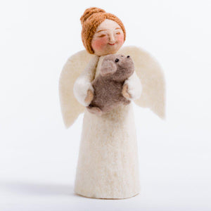 A handmade felt angel ornament with white skin wearing white with white wings and a brown bun holding a small brown dog in her arms.