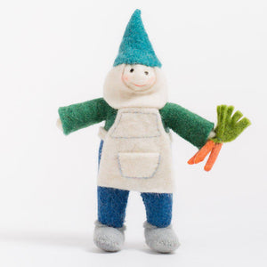 A handmade Craftspring gnome ornament wearing a blue pointy cap and white apron holding a handful of carrots