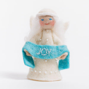 A Craftspring handmade felt angel ornament with a beaded dress white circlet and holding a blue sash embroidered with the word joy