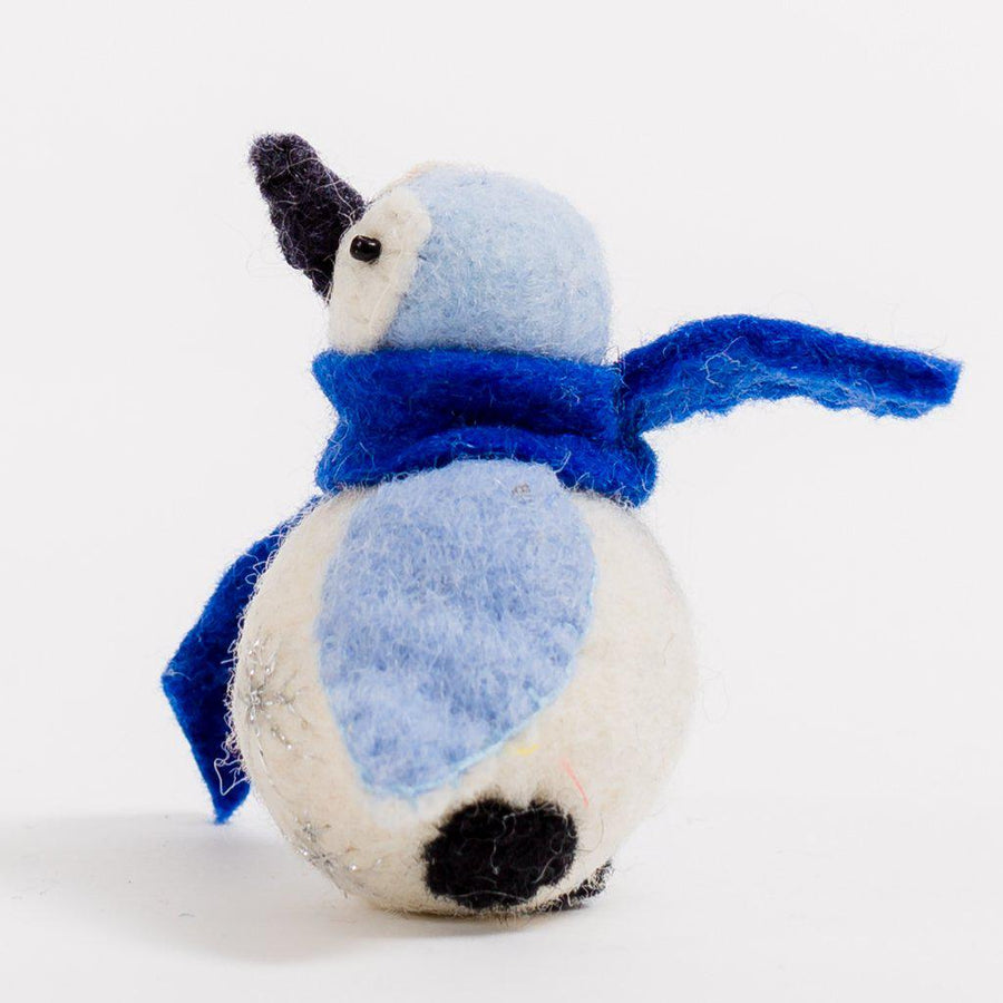 A Craftspring handmade felt penguin ornament with embroidered silver snowflake on their tummy and wearing a blue scarf