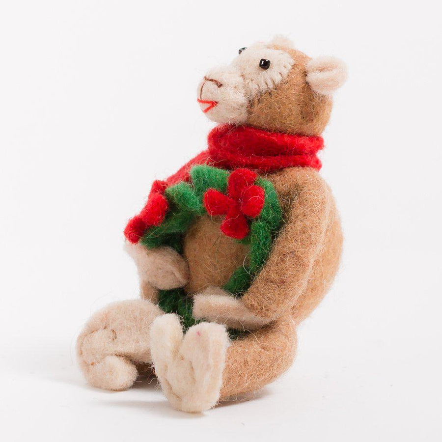 A Craftspring handmade felt monkey ornament wearing a red scarf holding a green wreath with red flowers