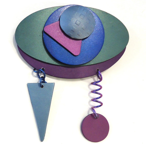 Handmade aluminum brooch made of layered shapes over an oval background in blue, green and purple