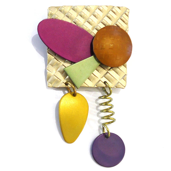 Square handmade aluminum brooch with layered geometric shapes in bright pink, yellow and purple
