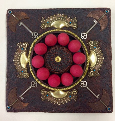 Square handmade paper wall sculpture with bright red wooden eggs, keys and metallic gold accents.