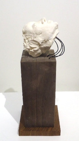 Small white clay female head gazing up, mounted by wire to wood block by Philadelphia artist Peggy O'Donnell