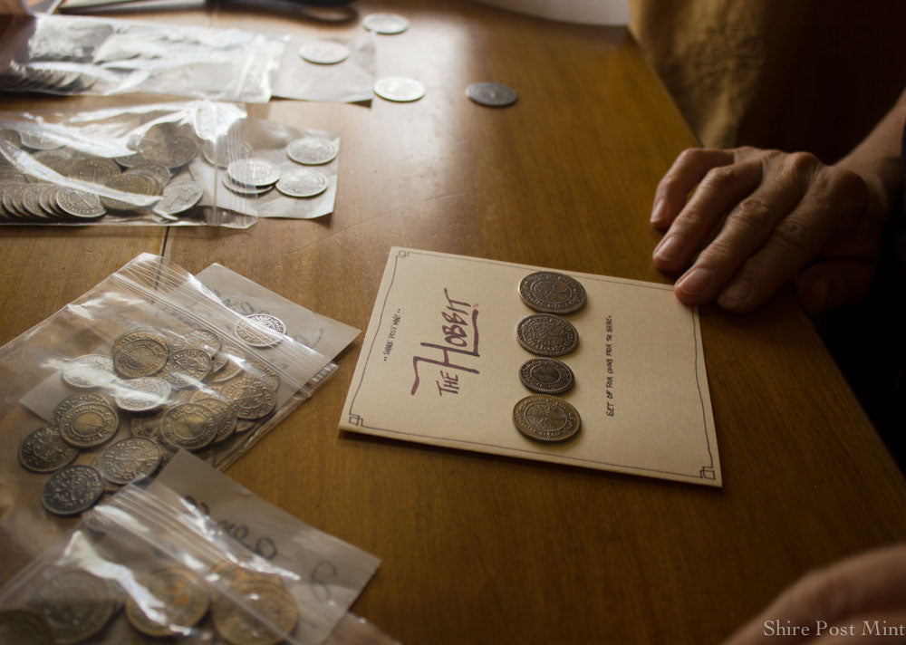 The Hobbit Set #2 being packaged onto a card with history and translations of each coin