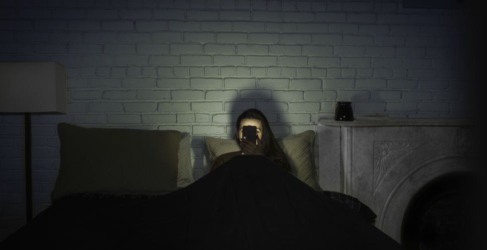 Woman in bed looking at phone at night