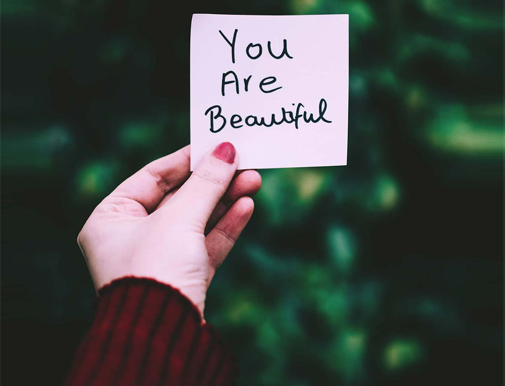 "A photo of a compliment on a sticky note being held up by one hand. It says ""You are beautiful""."