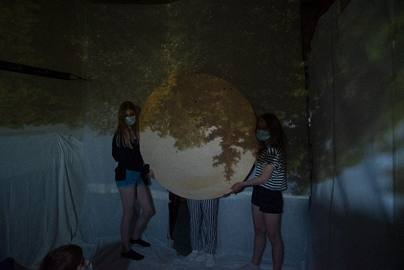 The children are holding a wooden board as a Camera obscura image frame.