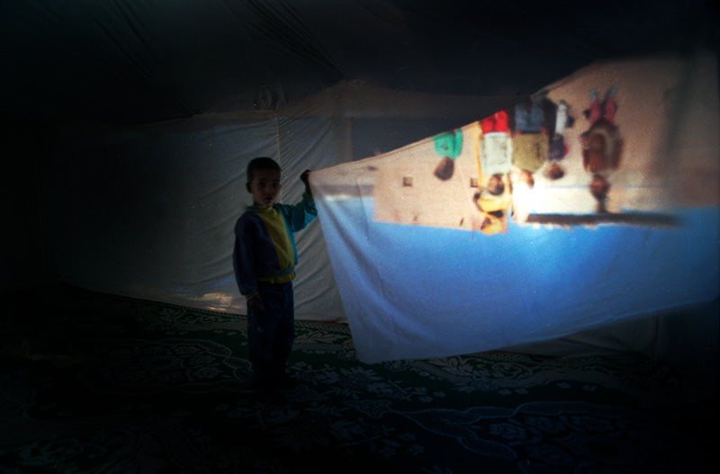 Schoolboy holding a projection. Camera Obscura project Western Sahara refugee camps 2004. Nilufar Nuthall
