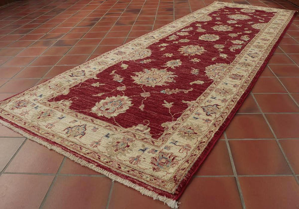 With its red background and cream border this Afghan runner has a welcoming look.