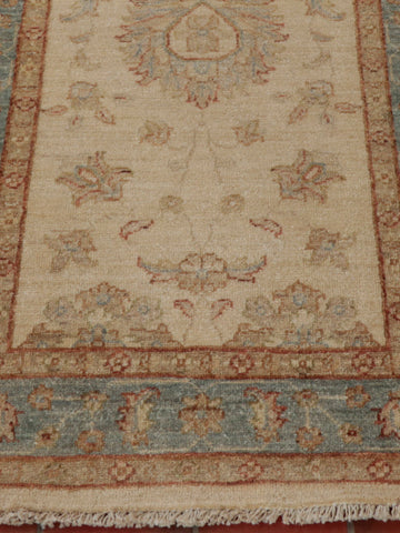 A hand knotted Afghan Ziegler runner with cream background and soft blue border.