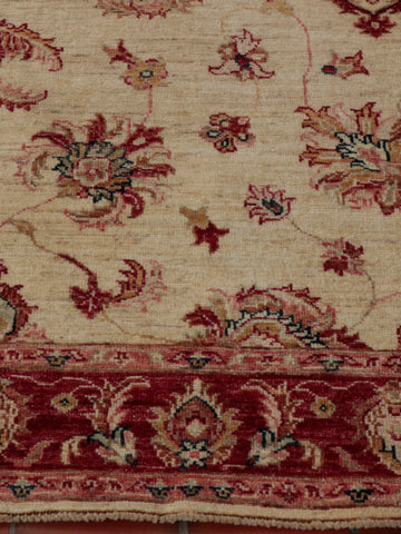 A hand knotted Afghan Ziegler runner with a cream background and soft red border.