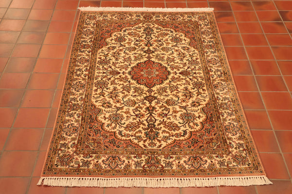Fine Kashmir silk rug which is hand-knotted silk on a cotton foundation. It has a cream ground with rose pink teal and green.