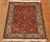 This is a highly decorated silk rug with a very detailed design.  A splendid red ground with florals in cream, greens and black.  There is a cream border with contrasting design using the same colour palette.