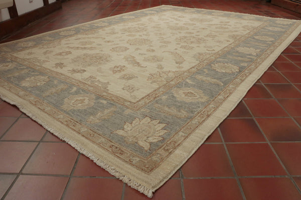 A cream background and a soft blue border have been used on this Afghan rug