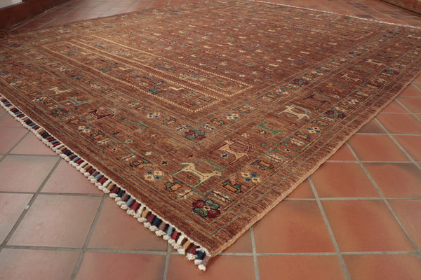 A hand made Afghan rug with a tribal theme incorporating animals.