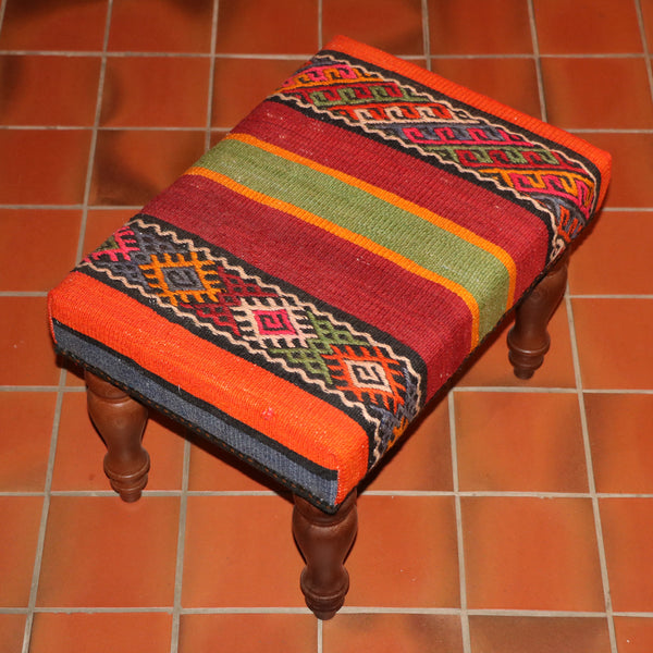 "a small footstool measuring 18"" x 14"" covered with a very vibrant old Turkish kilim. the colours are quite bold, orange red green gold blue and even a hint of pink."
