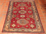 A good example of a traditional hand knotted Afghan Kazak rug showing a lively geometric design on a rich red background - 274196