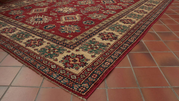 This Afghan Kazak has a rich red background, a cream border, different shades of blue, gold and green.