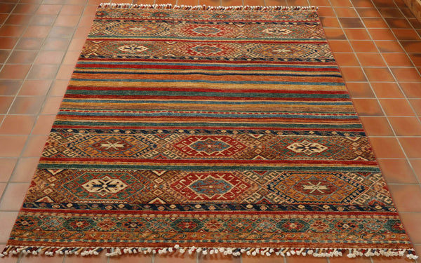 This beautiful Afghan Samarkand rug is a real kaleidoscope of colour. The design is a mix of stripes, with wide bands of traditional geometric designs at either end and the middle section consists of narrow plain bands of colour. The colours used are rich tomato red, old gold, terracotta, light and dark blue, cream and a wonderful sea green shade.