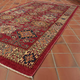 This fine Afghan Kazak rug has been made using a wool pile in red, blues, gold and cream colourings.