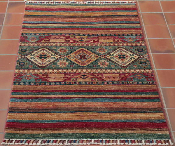 This hand made rug capture the essence of a Samarkand piece it is heavily banded with vary widths of stripe rich sultry colours of the east. Blues yellows and reds dominate the bands.