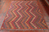 This wonderful Kilim is rather unusual in it design. From its ombre like peachy-pink ground to its violet, cream, jade, yellow, and blue geometric designs that form zig-zag style patterns across the marvellous piece.