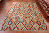 This Afghan Kilim rug is marvellous. its allover geometric patterning and contrasting colour palette make for a truly excellent piece of art. The cocktail of blues used, such as Carolina and steel blue, have been masterfully combined with contrasting touches of tangerine, crimson and mink. Whilst the piece is brought together in an expert fashion by cream, beige and straw yellow elements.