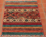 This wonderfully playful Afghan Samarkand possesses a traditional geometric central design that is top-and-tailed by, more contemporary, striped colour blocks. This piece features a combination of ruby reds, raw siennas, soft peaches, a multitude of brown tones, and turquoises - which all combine together to give this piece a sense of joyous, playful, liveliness.