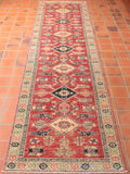 This bright and playful Kazak runner features a prominent rose red colour throughout — finely contrasted by the touches of Carolina and cobalt blues, present in the central patterning and boarders. The delicate inclusion of the warm cream and subtle washed jade, result in a well balanced colour palette.