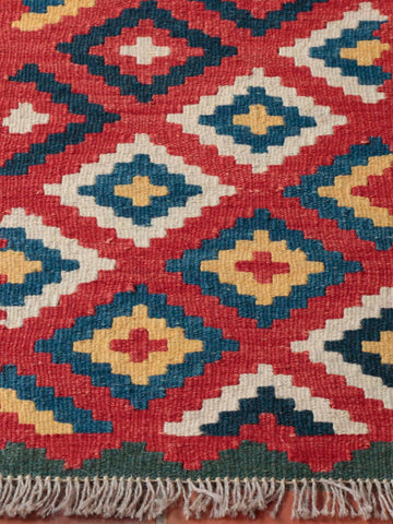 This kelim has a strong red ground, contrasted by a jade boarder and blue central designs.