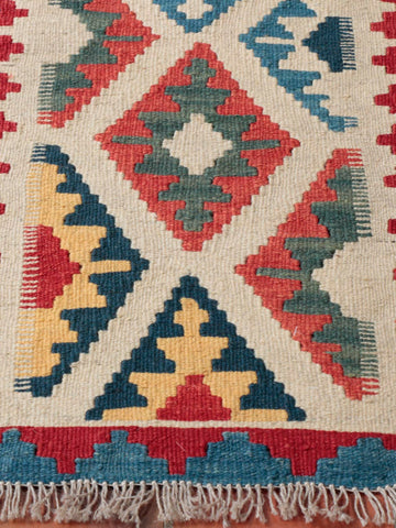 This Persian kelim has a vibrant and contrasting blue and red boarder, whereas the centre ground is a soft beige with elements of peachy-red and dew yellow punctuated by some darker blue or green.