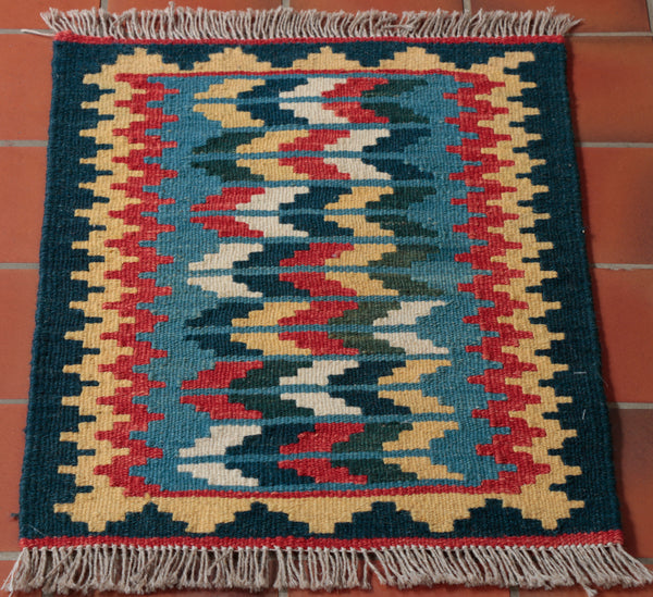 This Persian kilim has a classic diamond border with a really interesting random design in the middle. the colours used are Dark green Gold Terracotta Mid blue and ivory, all of which result in a vibrant small kelim