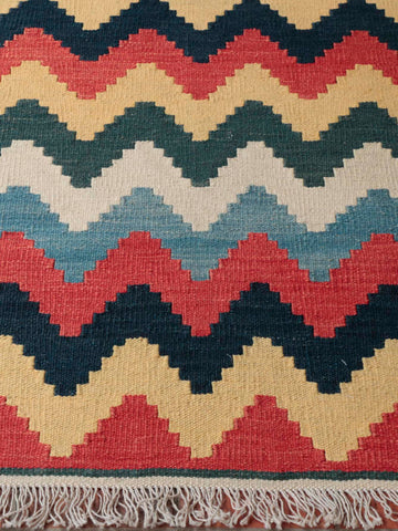 the weave in this kelim is well done and interesting with a zig zg pattern of gold terracotta green and blue/black