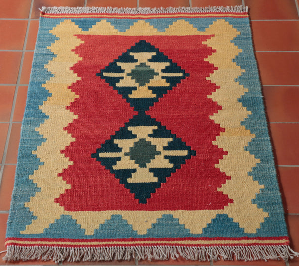 a small kelim which is 92 x 60cm which has a rich red ground on which we have two central  medallions in dark blue and sand colour