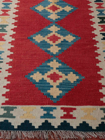 This Kilim is a lovely rich red center ground with a diamond lozenge pattern in the middle