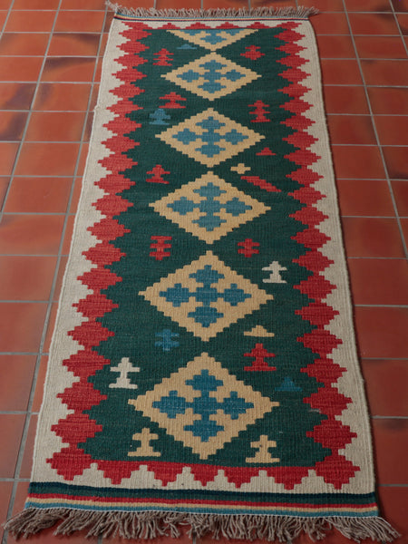 this is a runner measuring 188cm x 62cm it is made from wool and has a dark green central panel with inset diamond panels of blue diamonds on wheat coloured background,