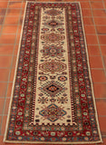 This Fine Afghan Kazak runner is rather light in its tonality, possessing a soft beige centre ground that is complemented by the contrasting touches of sage green, crimson red, Carolina blue, and delicate pink.