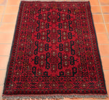 A wonderfully geometric Afghan Khan Mohammadi rug - combining a strong currant red with significant areas of contrasting blue-black and touches of beige. The fringe on this piece is a soft mid-grey.