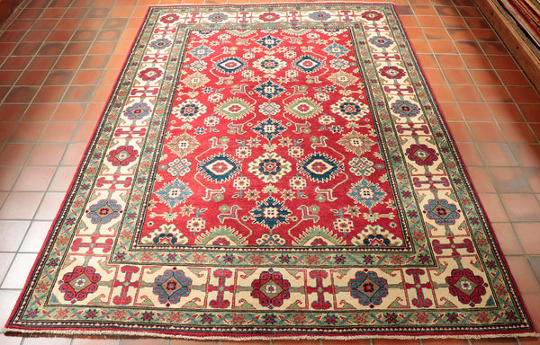 The marvellous vibrancy that this Afghan Kazak bestows has been caused by a commercial dyeing process rather than a natural one. Ultimately resulting in the featured ruby red, Carolina and cobalt blue, fern green, warm beige colours being rather bright and distinct.