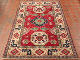 This bright Afghan Kazak features a rather vibrant colour palette, a result of the commercial dyeing process hat this piece has undergone, combining strong crimson reds with darker cobalt blues, washed jade greens, and large amounts of beige.