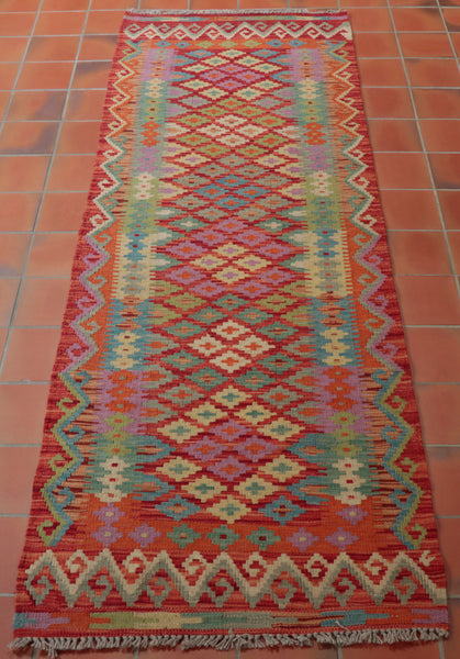 This brightly coloured Afghan kilim runner would brighten up any floor.