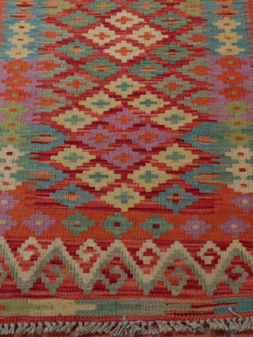 Bright rich colours of red, blue, cream, purple and green used in the Afghan kilim runner.